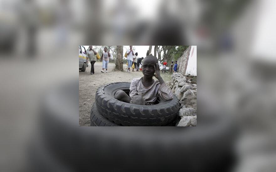 Vaikas ilsisi sėdėdamas panaudotose padangose (Kenija).