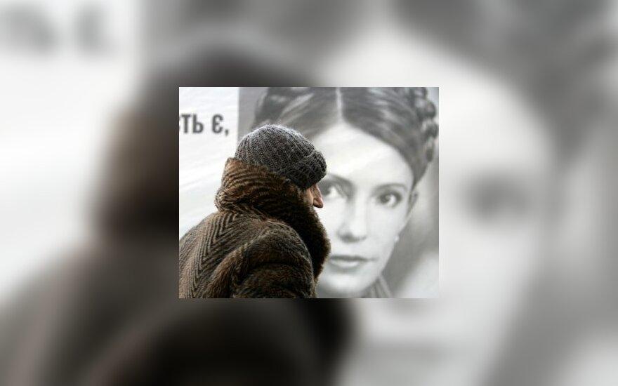 Pagyvenusi moteris eina pro Julijos Tymošenko rinkiminį plakatą Kijevo (Ukraina) centre.