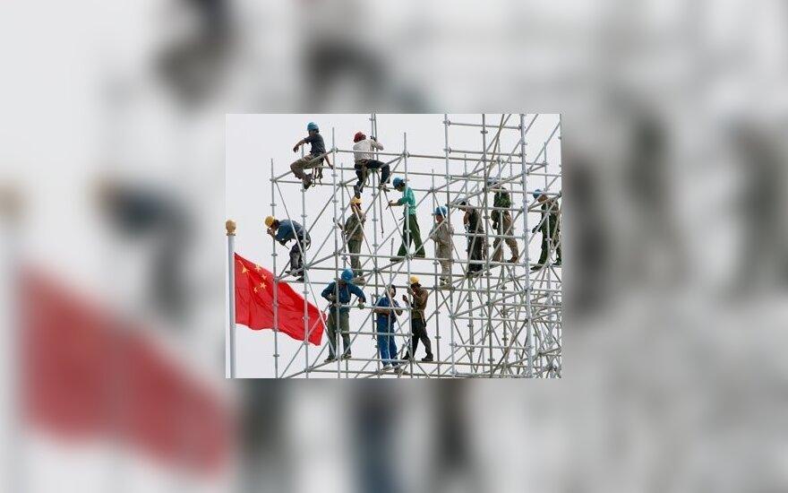 """Kinijos darbininkai """"Metų iki Pekino olimpiados"""" šventei montuoja didelę sceną."""