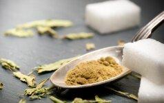Džiovinti stevijos lapeliai ir iš stevijų gauta pudra, šalia balto rafinuoto cukraus
