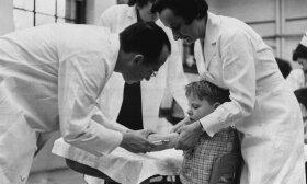 Skiepai nuo poliomielito. Vaiką skiepija vakcinos atradėjas amerikietis Jonas E. Salk / 1954 m.