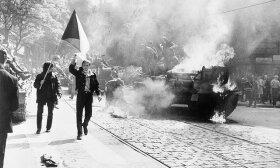 Sovietų Sąjungos įsiveržimas į Čekoslovakiją. Čekoslovakai neša nacionalinę vėliavągreta degančių sovietų tankų. 1968. Praha