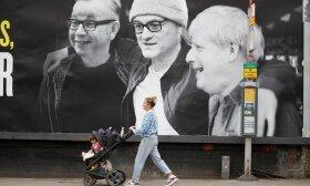 Moteris su kūdikiu eina pro afišą, kurioje pavaizduoti Lankasterio hercogystės kancleris Michaelas Gove, JK premjero specialusis patarėjas Dominicas Cummingsas ir JK ministras pirmininkas Borisas Johnsonas