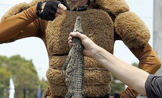 """Gatvės artistas, apsirengęs kengūros kostiumu, """"šnekina"""" krokodiliuką."""