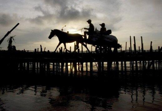 Kambodžos ūkininkas rieda bambukiniu tiltu