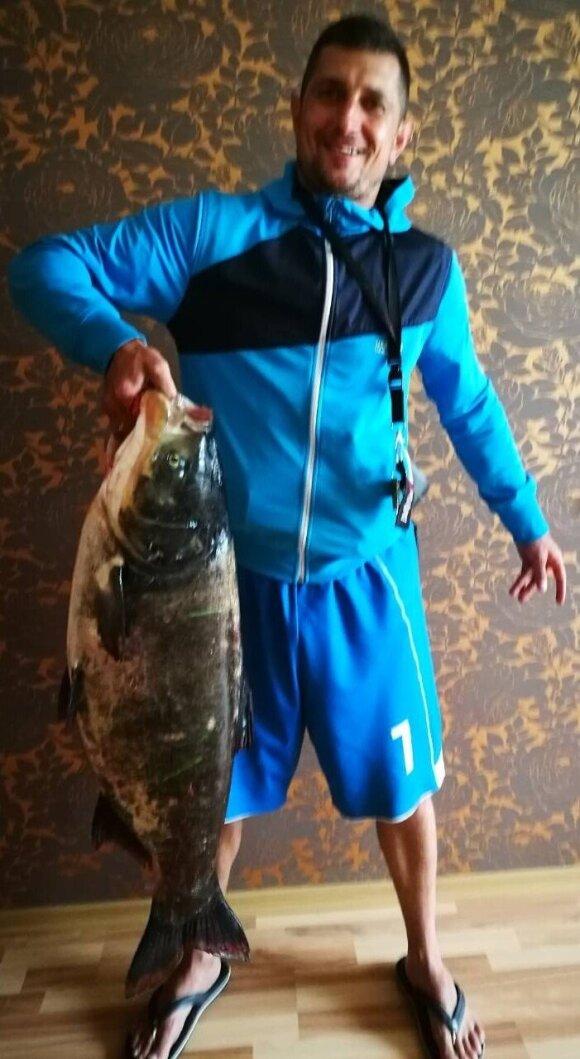 Žvejys didžiuojasi tvenkinyje sugautu laimikiu