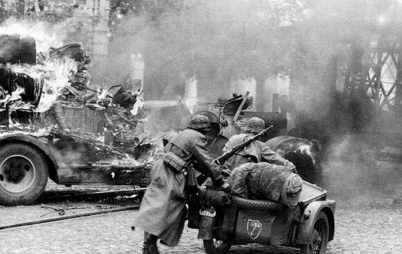 """SS tankų divizijos kariai važiuoja motociklu """"Zündap KS-750"""" Rytų fronte per užimtą miestą. 1941 m."""