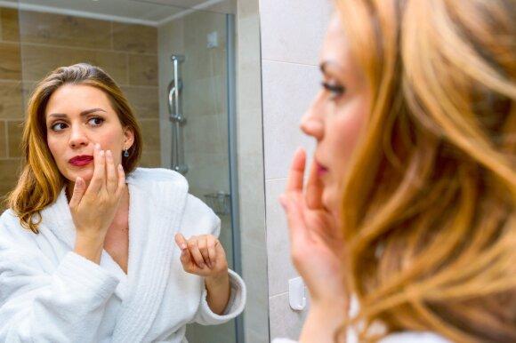 Moteris prie veidrodžio.