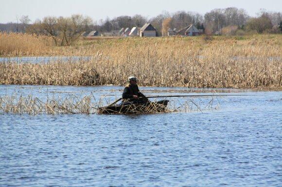 Žvejas medinėje valtelėje
