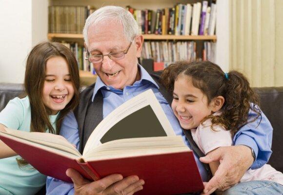 Senelis su anūkėmis skaito knygą