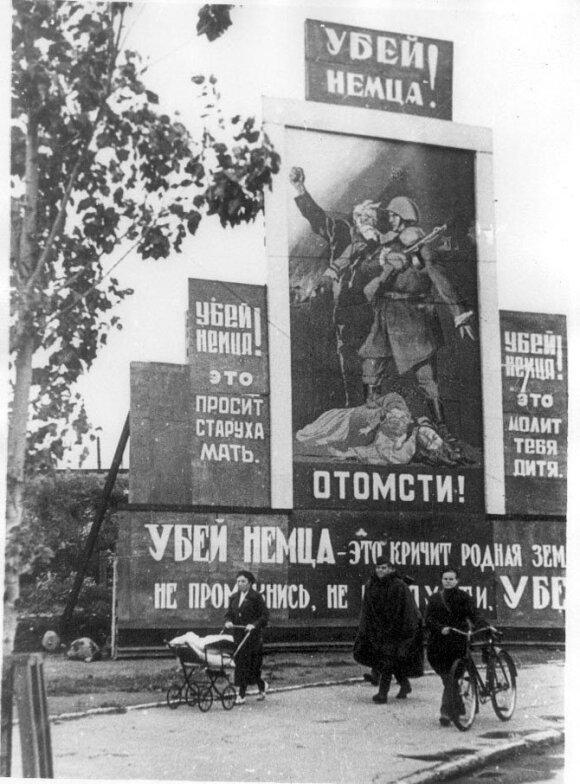 """Raudonojo propagandininko I. Erenburgo darbo vaisiai. Stendas Leningrade skelbia: """"Nužudyk vokietį! Atkeršyk!"""", """"Nužudyk vokietį! Prašo tave senutė motina"""", """"Nužudyk vokietį! Meldžia kūdikis!"""""""
