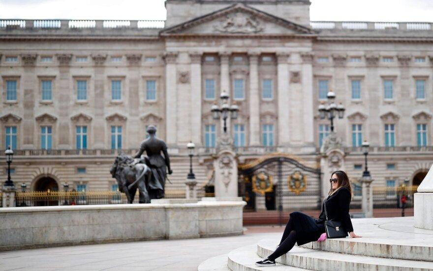 Moteris sėdi ant laiptų priešais Bekingemo rūmus Londone