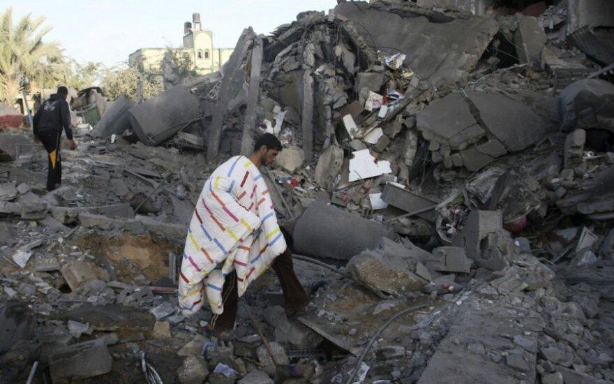 Palestinietis renka daiktus iš Izraelio atakuoto Hamas karinio lyderio Attia Abu Inkara namo