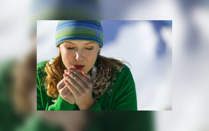Moteris šildo rankas
