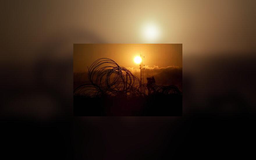 Saulė kyla virš kariškių bazės buvusioje žydų naujakurių gyvenvietėje Kfar Darome, Gazos ruože.