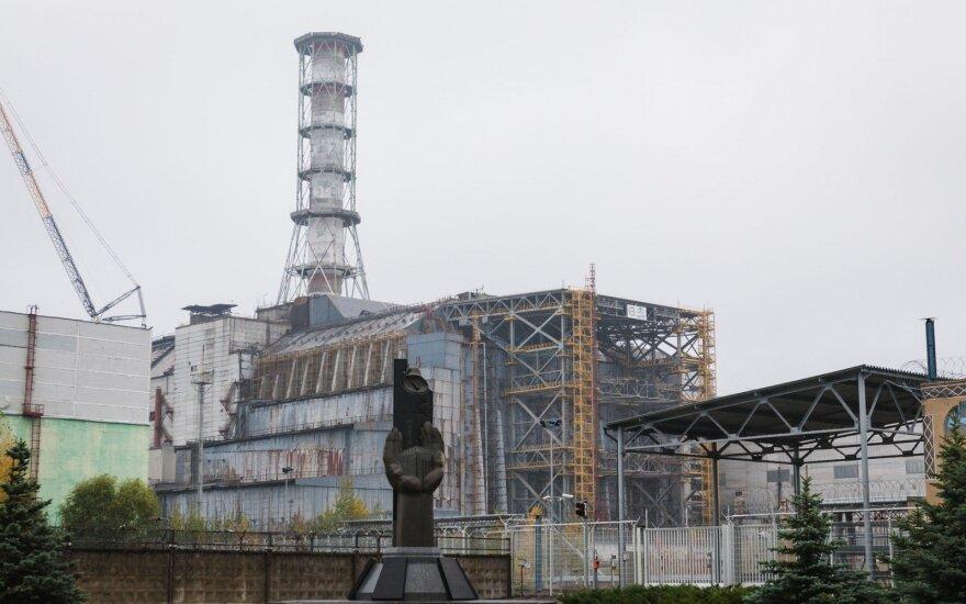 Černobylio AE ketvirtojo bloko sarkofagas ir kombinuotoji stabilizuojanti plieno konstrukcija. Priešais monumentas didvyriams – profesionalams, likvidavusiems katastrofos padarinius. Andrew Leatherbarrow nuotrauka.