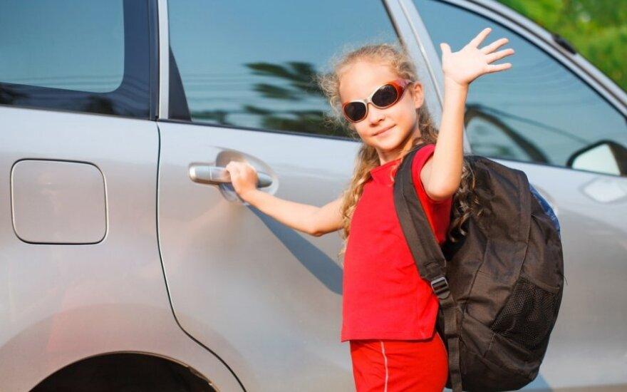 Mergaitė su kuprine prie automobilio