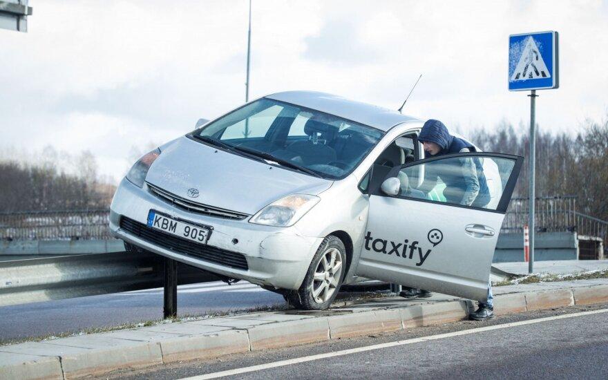 """Vilniuje """"Taxify"""" automobilis užlėkė ant atitvarų, nelaimėlio kolega puolė fotografą"""