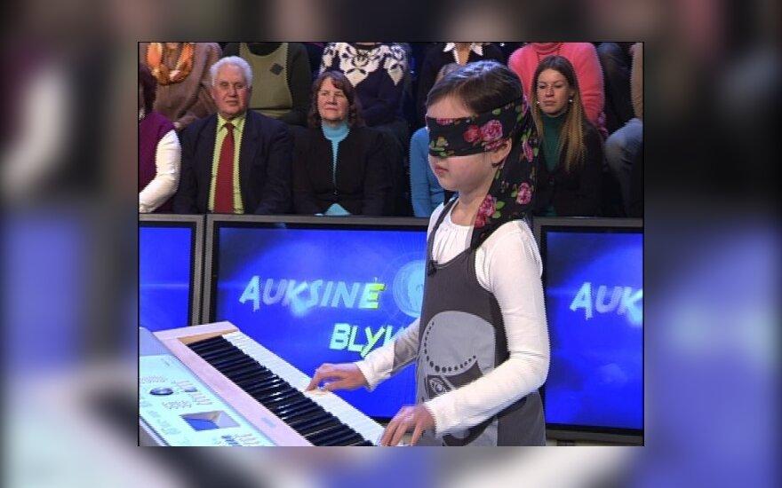 """""""2 minutės šlovės"""" dalyvė aštuonmetė užrištomis akimis vienu metu groja pianinu ir žaidžia šachmatais"""