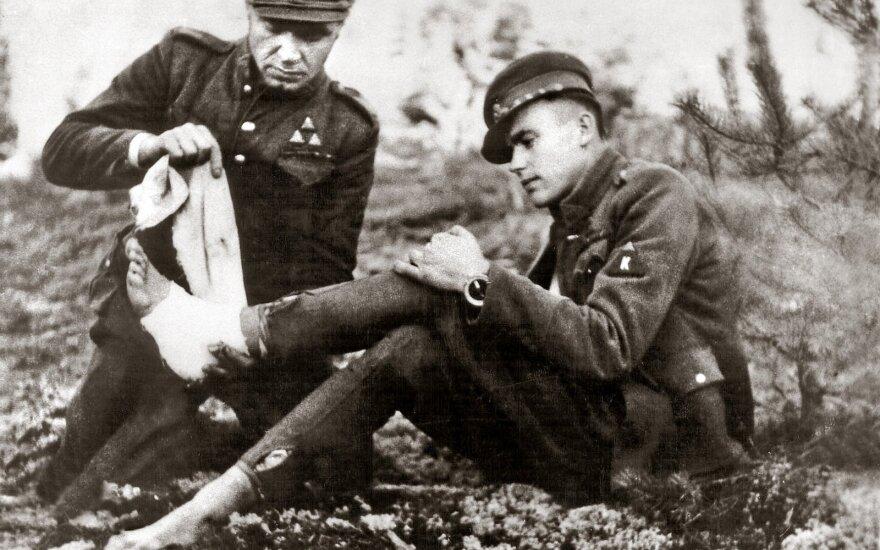 Dainavos apygardos partizanas Feliksas Daugirdas-Šarūnas bintuoja koją bendražygiui Vincui Kalantai-Nemunui. Apie 1949 m.