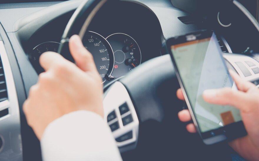 Vairuotojas su telefonu rankose