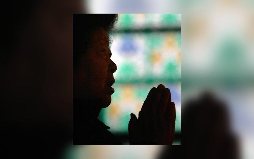 Pekino bažnyčioje moteris meldžiasi už mirusį popiežių.