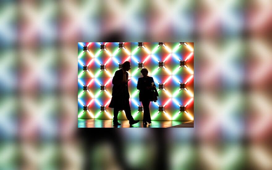 "Du žmonės eina menininko Johno Armlederio darbo fone parodoje ""Kelno menas 2005"" (Art Cologne 2005)."