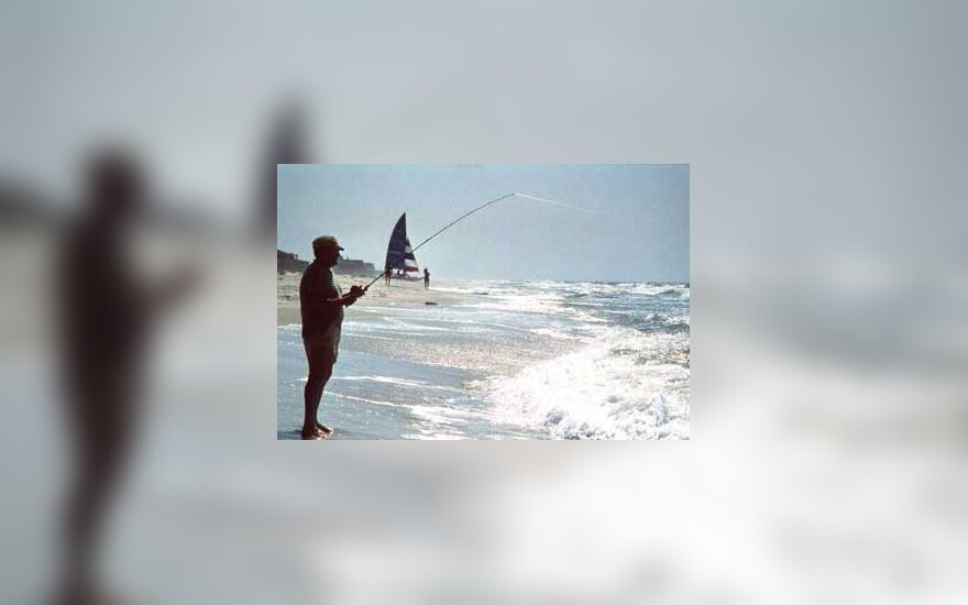 Man fishes off the beach