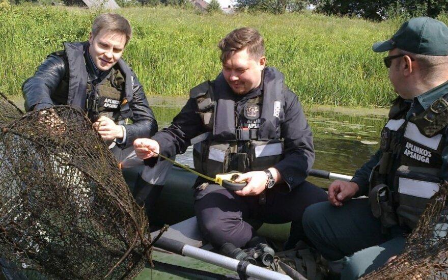 Viceministras A. Petkus su aplinkosaugininkais matuoja iš vandens ištrauktą gaudyklę