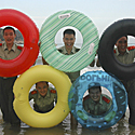 Apsaugos darbuotojai pozuoja su plaukimo ratais, simbolizuojančiais Olimpiados žiedus