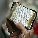 Besimeldžiantis vyras skaito iš mažos Korano kopijos