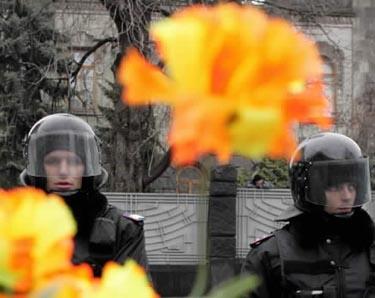 Milicininkai stovi už tvoros, išpuoštos opozicijos kandidato V.Juščenkos rėmėjų atneštomis gėlėmis.