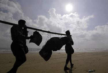 Indė, išgyvenusi cunamį,  stebi sugriuvusių namų liekanas.