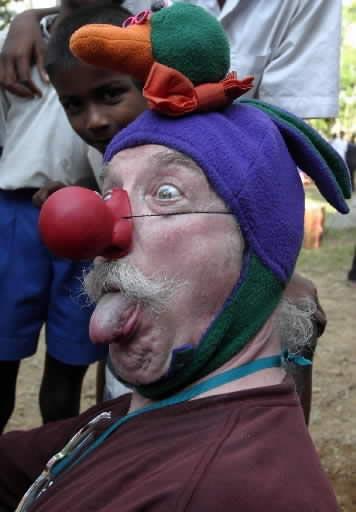 Amerikiečių juoko terapeutas Patchas Adamsas žaidžia su cunamį išgyvenusiais našlaičiais.