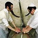 Žydų ortodoksai minko tešlą macams.
