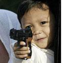 Filipinietis berniukas žaidžia su žaisliniu ginklu.